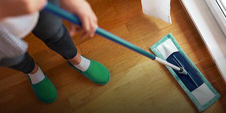 Imagem de uma profissional passando pano no chão