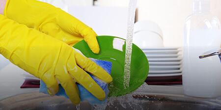 Imagem de uma profissional lavando um prato