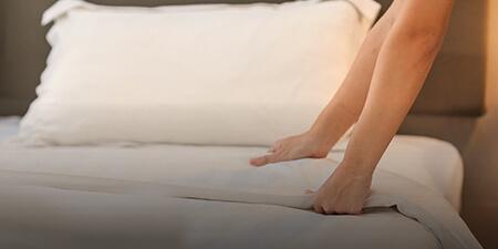 Imagem de uma profissional arrumando uma cama